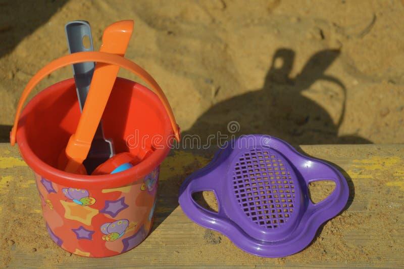 Παιχνίδια παιδιών για το Sandbox, τον κάδο, το φτυάρι και την τσουγκράνα στοκ φωτογραφία