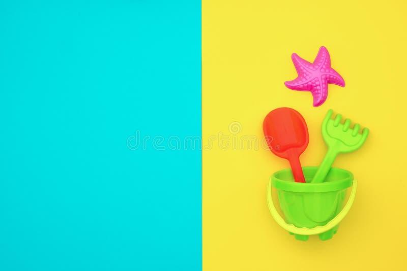 Παιχνίδια των πολύχρωμων καθορισμένων παιδιών για τους θερινούς αγώνες στο Sandbox ή στην αμμώδη παραλία στο μπλε κίτρινο υπόβαθρ στοκ εικόνες