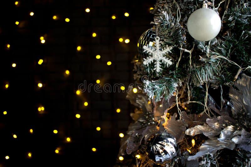 Παιχνίδια Χριστουγέννων στο δέντρο πεύκων Άσπρο snowflake, πορτοκαλιές λάμπες φωτός και σφαίρες Σκοτεινή ανασκόπηση στοκ εικόνες με δικαίωμα ελεύθερης χρήσης