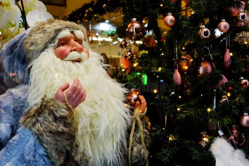 Παιχνίδι Άγιος Βασίλης για την πώληση στο κατάστημα στο υπόβαθρο του χριστουγεννιάτικου δέντρου και των λαμπτήρων φω'των στοκ εικόνα