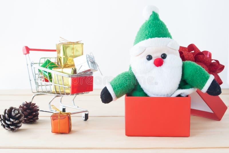 Παιχνίδι Άγιου Βασίλη στο κόκκινο κιβώτιο δώρων με το κάρρο αγορών, πλήρες των κιβωτίων δώρων, Χαρούμενα Χριστούγεννα στοκ εικόνες