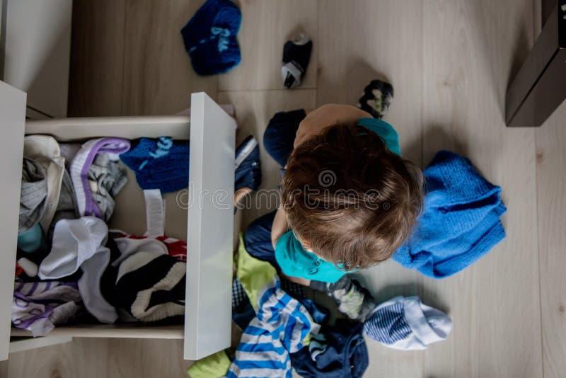 Παιχνίδι αγοριών με τα ενδύματα από το ντουλάπι στοκ φωτογραφία