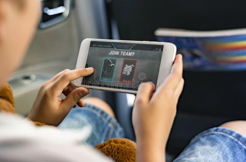 Παιχνίδι αγοριών σε ένα smartphone στο αυτοκίνητο στοκ εικόνες