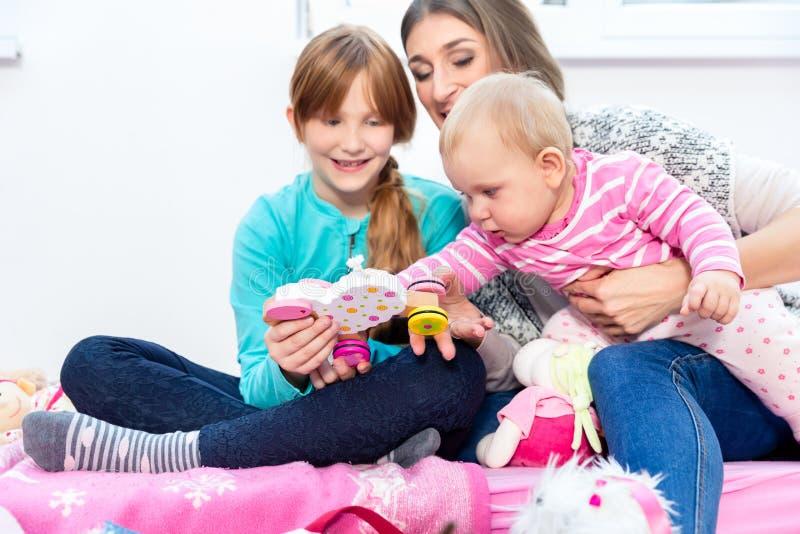 Παιχνίδι αδελφών και μητέρων με το μωρό στοκ φωτογραφία