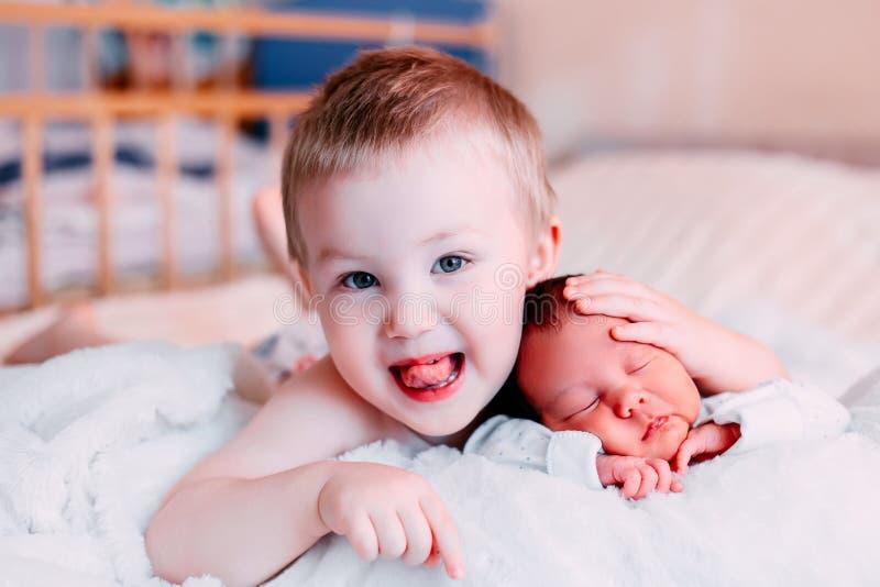 παιχνίδι αδελφών μικρών παιδιών με το νεογέννητο μωρό ύπνου στοκ εικόνες