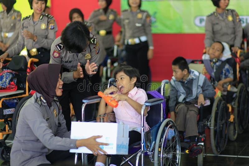 Παιχνίδι γυναικών αστυνομίας με τα παιδιά ανάπηρα στοκ φωτογραφία με δικαίωμα ελεύθερης χρήσης