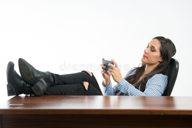 Παιχνίδι γυναικών στο κινητό τηλέφωνο στο γραφείο, που κάθεται με τα πόδια στο δ στοκ εικόνες
