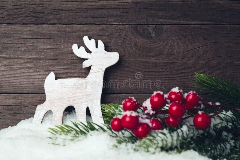 Παιχνίδι και δέντρο ελαφιών Χριστουγέννων στο χιόνι πέρα από το ξύλινο υπόβαθρο στοκ εικόνες