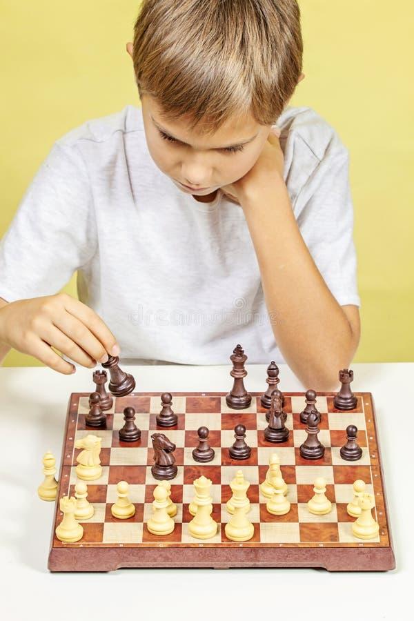 παιχνίδι κατσικιών σκακι&omi Αγόρι που εξετάζει τον πίνακα σκακιού και που σκέφτεται για τη στρατηγική του στοκ φωτογραφίες