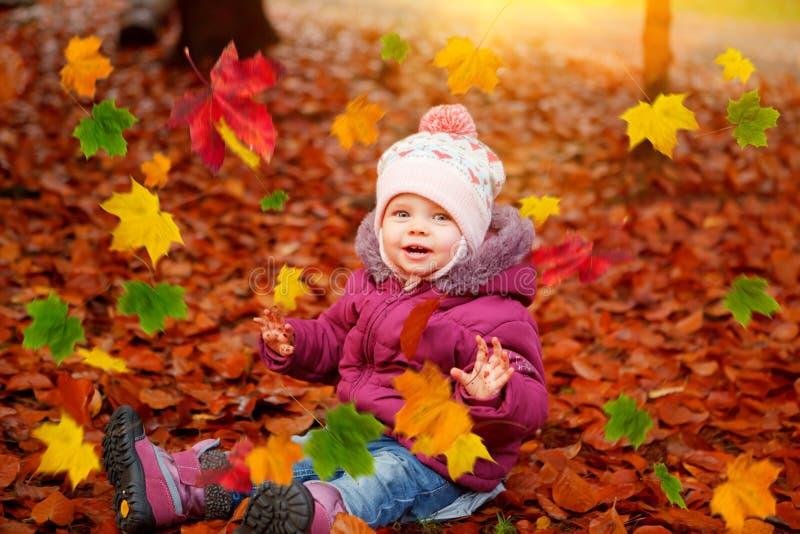 Παιχνίδι κοριτσάκι με τα φύλλα φθινοπώρου στοκ εικόνα
