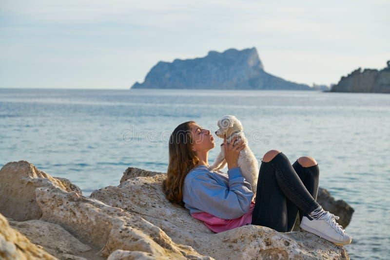 Παιχνίδι κοριτσιών με το σκυλί maltichon στην παραλία στοκ εικόνα