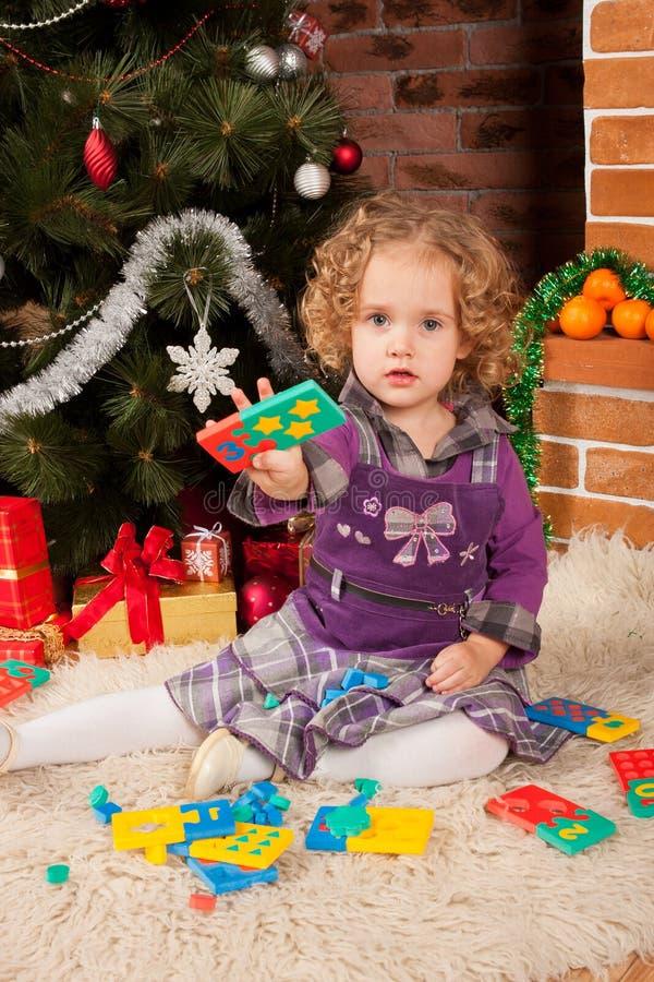 Παιχνίδι μικρών κοριτσιών κοντά στο χριστουγεννιάτικο δέντρο στοκ εικόνα