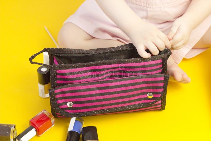 Παιχνίδι μικρών κοριτσιών με την καλλυντική στιλβωτική ουσία τσαντών και καρφιών, κίτρινο καλλυντικό υποβάθρου στοκ εικόνες με δικαίωμα ελεύθερης χρήσης