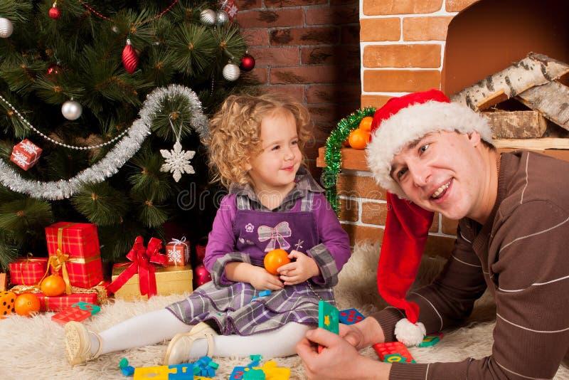 Παιχνίδι μικρών κοριτσιών με τον μπαμπά κοντά στο χριστουγεννιάτικο δέντρο στοκ εικόνες
