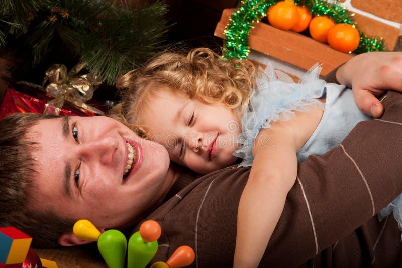 Παιχνίδι μικρών κοριτσιών με τον μπαμπά κοντά στο χριστουγεννιάτικο δέντρο στοκ φωτογραφία