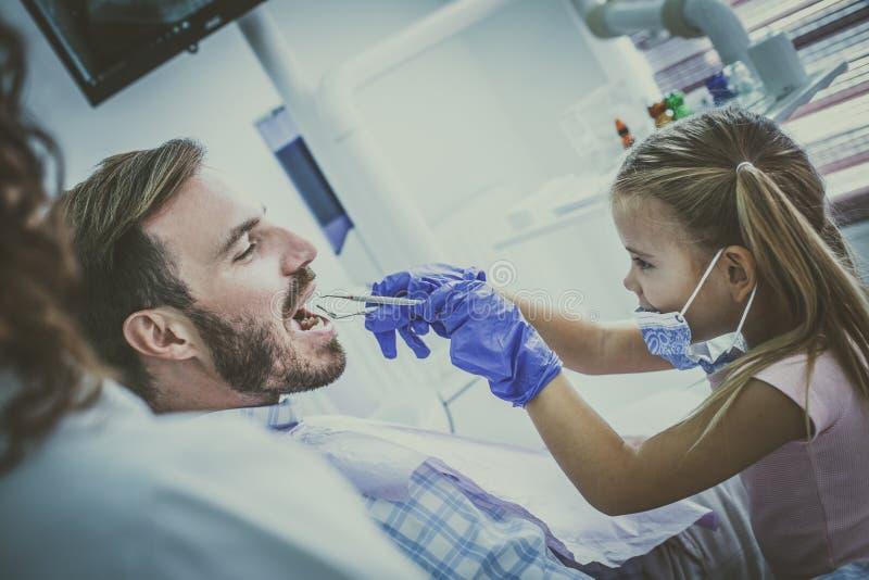 Παιχνίδι μικρών κοριτσιών με τον πατέρα της στο γραφείο οδοντιάτρων στοκ εικόνα με δικαίωμα ελεύθερης χρήσης