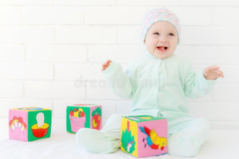 Παιχνίδι μικρών κοριτσιών με τους ζωηρόχρωμους κύβους στοκ εικόνα με δικαίωμα ελεύθερης χρήσης