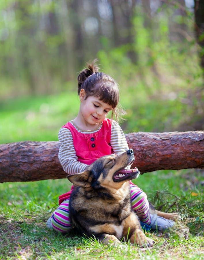Παιχνίδι μικρών κοριτσιών με το σκυλί στοκ φωτογραφία