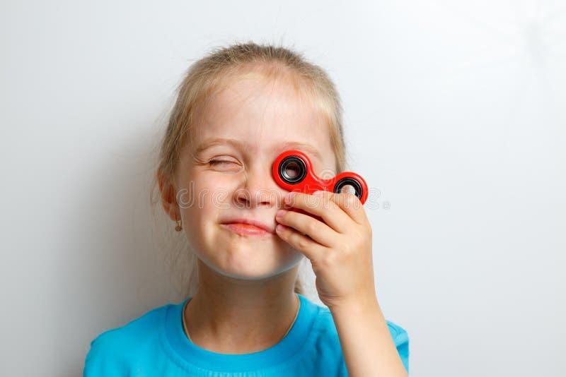 Παιχνίδι μικρών κοριτσιών με fidget τον κλώστη στοκ φωτογραφία με δικαίωμα ελεύθερης χρήσης