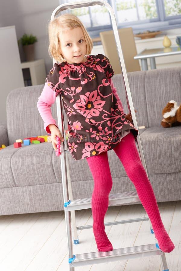 Παιχνίδι μικρών κοριτσιών στη σκάλα στο καθιστικό στοκ εικόνες