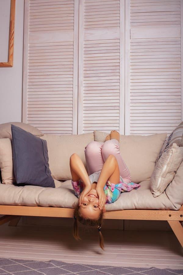 Παιχνίδι μικρών κοριτσιών στον καναπέ Η έννοια της παιδικής ηλικίας και του λ στοκ εικόνες με δικαίωμα ελεύθερης χρήσης