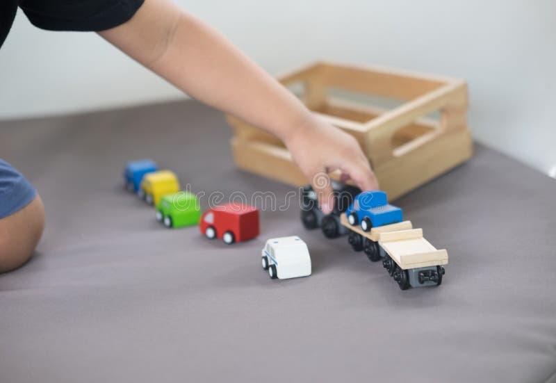 Παιχνίδι μικρών παιδιών με ένα ζωηρόχρωμο ξύλινο αυτοκίνητο παιχνιδιών στοκ εικόνες