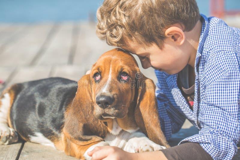 Παιχνίδι μικρών παιδιών με αναπαραγμένο το σκυλί κυνηγόσκυλο μπασέ του κοντά στη θάλασσα στοκ εικόνες