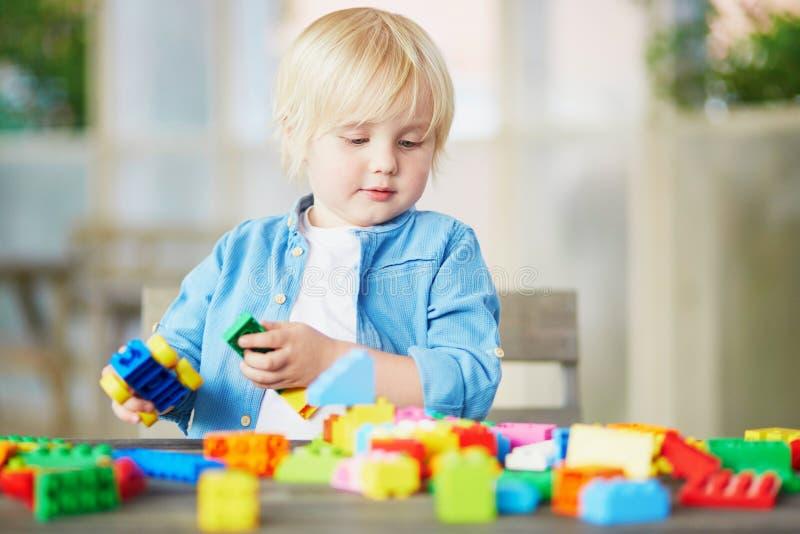 Παιχνίδι μικρών παιδιών με τους ζωηρόχρωμους πλαστικούς φραγμούς κατασκευής στοκ φωτογραφίες