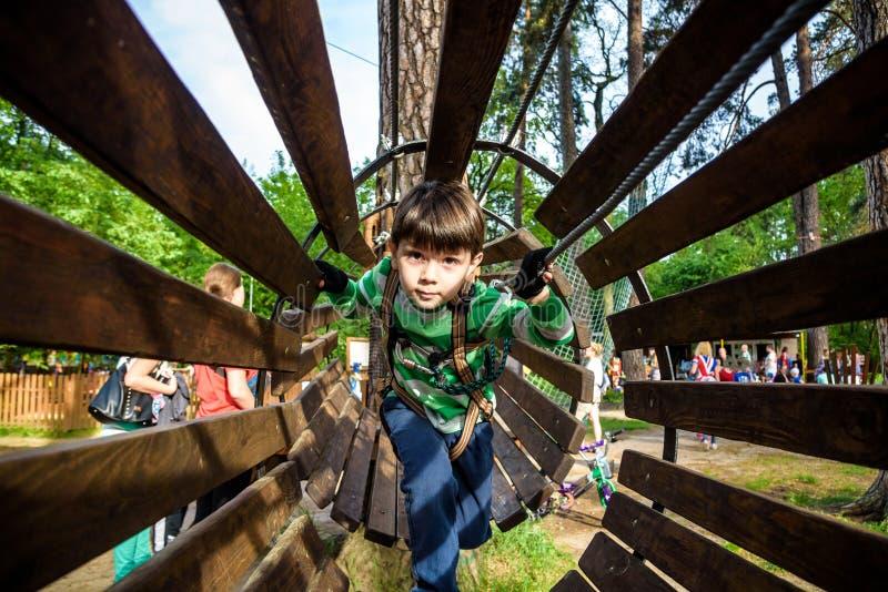 Παιχνίδι μικρών παιδιών στο πάρκο περιπέτειας σχοινιών Έννοια καλοκαιρινών διακοπών Χαριτωμένο παιδί που έχει τη διασκέδαση στην  στοκ εικόνες με δικαίωμα ελεύθερης χρήσης