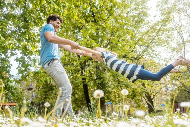 Παιχνίδι μπαμπάδων με την κόρη του στη χλόη στοκ φωτογραφίες