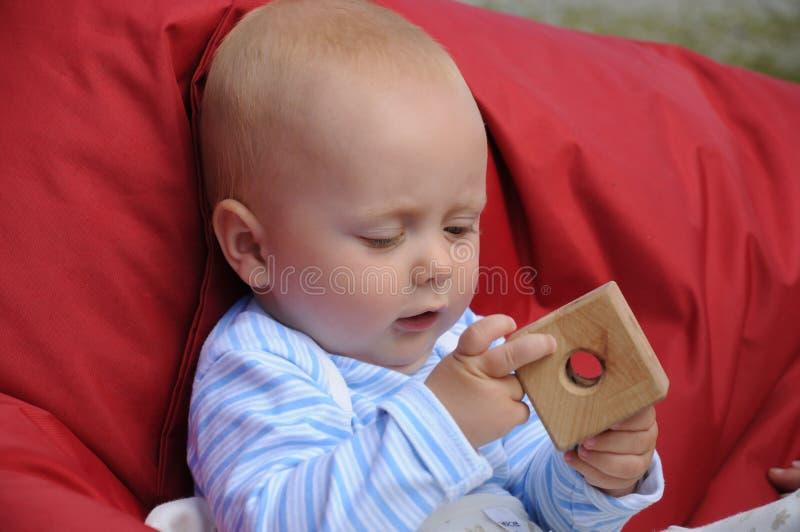 Παιχνίδι μωρών με τον ξύλινο κύβο στοκ φωτογραφίες