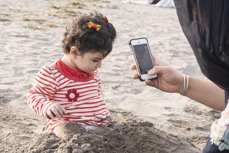 Παιχνίδι παιδάκι στην παραλία με την άμμο και τη μητέρα της που παίρνει το π στοκ εικόνες