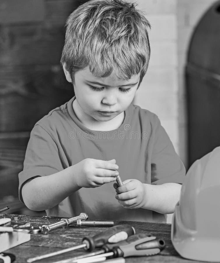 Παιχνίδι παιδιών κινηματογραφήσεων σε πρώτο πλάνο με τα μπουλόνια μετάλλων Λίγο laborer στο εργαστήριο Χαριτωμένο αγόρι στην κόκκ στοκ εικόνα