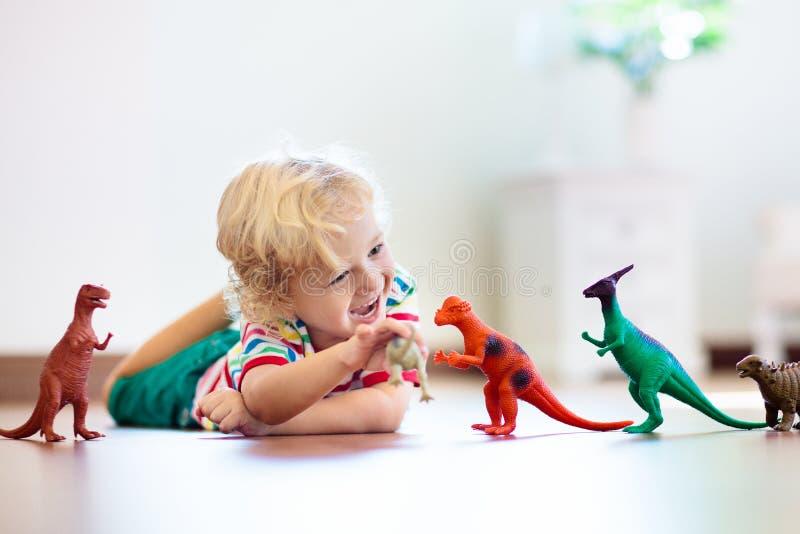 Παιχνίδι παιδιών με τους δεινοσαύρους παιχνιδιών Παιχνίδια παιδιών στοκ φωτογραφία