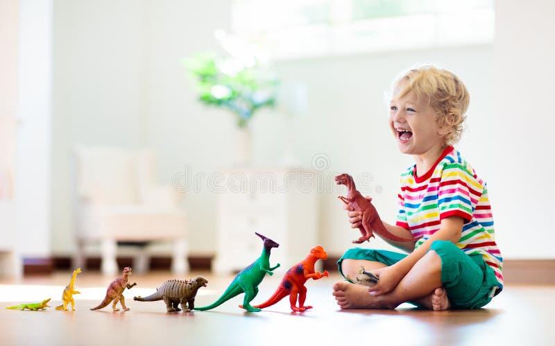 Παιχνίδι παιδιών με τους δεινοσαύρους παιχνιδιών Παιχνίδια παιδιών στοκ εικόνες