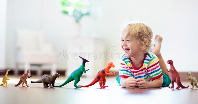 Παιχνίδι παιδιών με τους δεινοσαύρους παιχνιδιών Παιχνίδια παιδιών στοκ εικόνα με δικαίωμα ελεύθερης χρήσης
