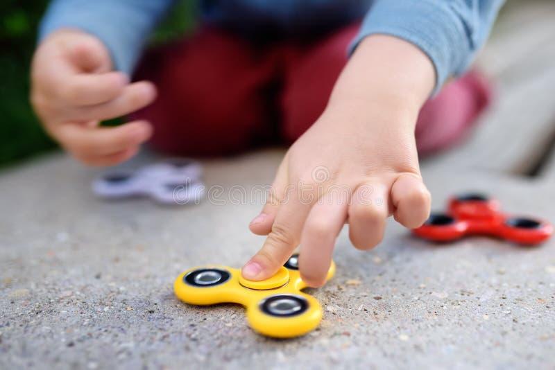Παιχνίδι παιδιών με τους δημοφιλείς περιστρεφόμενους fidget κλώστες στοκ εικόνες