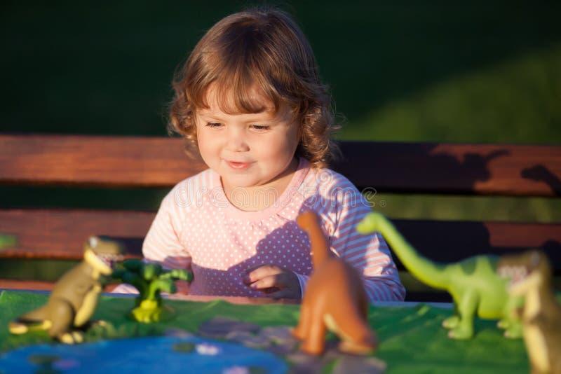 Παιχνίδι παιδιών μικρών παιδιών με έναν δεινόσαυρο παιχνιδιών στοκ εικόνα με δικαίωμα ελεύθερης χρήσης