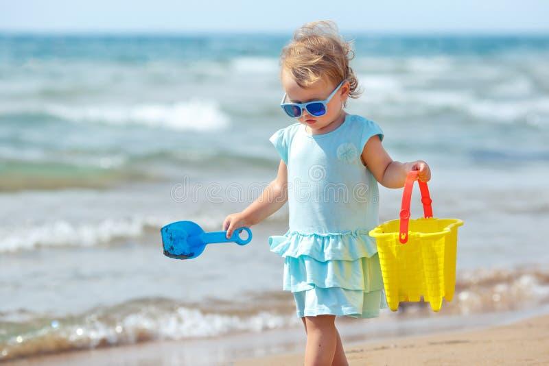 Παιχνίδι παιδιών στην τροπική παραλία Εν πλω ακτή άμμου μικρών κοριτσιών σκάβοντας Παιχνίδι παιδιών με τα παιχνίδια άμμου Ταξίδι  στοκ φωτογραφία