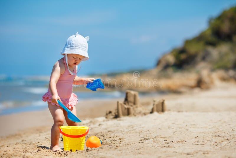Παιχνίδι παιδιών στην τροπική παραλία Η σκάβοντας άμμος μικρών κοριτσιών και χτίζει μια εν πλω ακτή κάστρων άμμου Παιχνίδι παιδιώ στοκ εικόνες με δικαίωμα ελεύθερης χρήσης