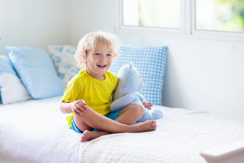 Παιχνίδι παιδιών στο κρεβάτι δωμάτιο κατσικιών Αγοράκι στο σπίτι στοκ φωτογραφία με δικαίωμα ελεύθερης χρήσης