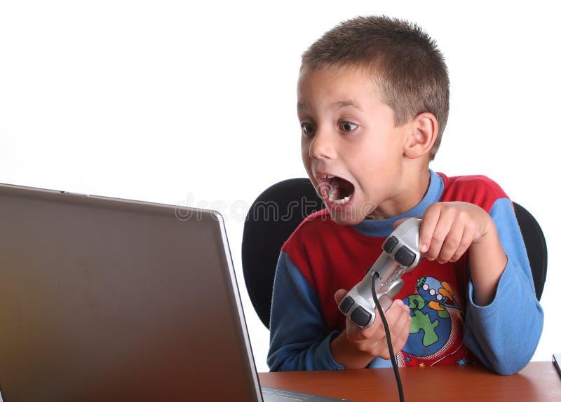 παιχνίδι παιχνιδιών στον υπολογιστή αγοριών στοκ φωτογραφία
