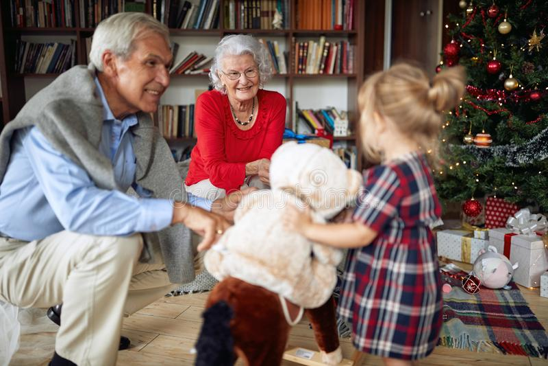 Παιχνίδι παππούδων και γιαγιάδων και μικρών κοριτσιών μαζί για τα Χριστούγεννα στοκ φωτογραφίες