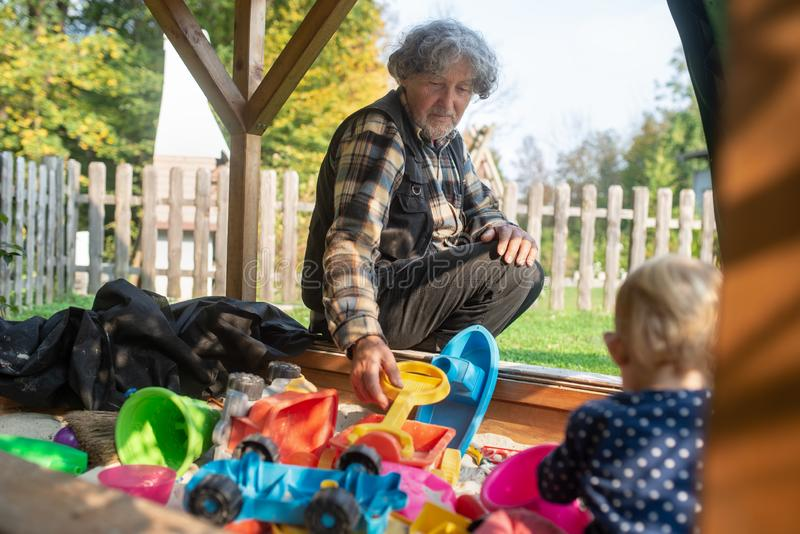 Παιχνίδι παππούδων με την εγγονή του σε μια άμμο στοκ φωτογραφία με δικαίωμα ελεύθερης χρήσης