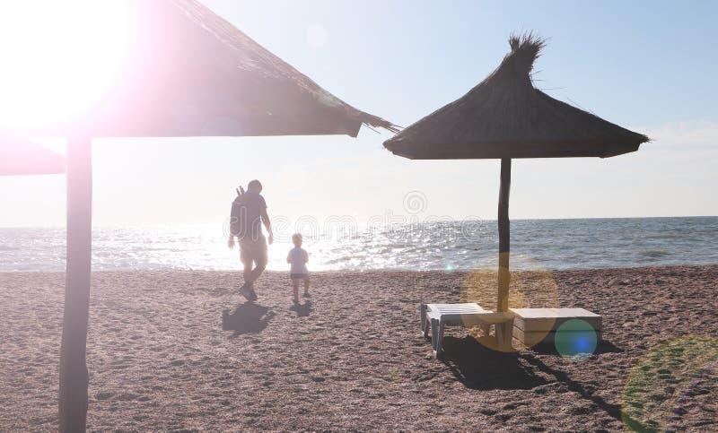 Παιχνίδι πατέρων και αγοριών στην παραλία στο χρόνο ηλιοβασιλέματος, έννοια της φιλικής οικογένειας στοκ εικόνες