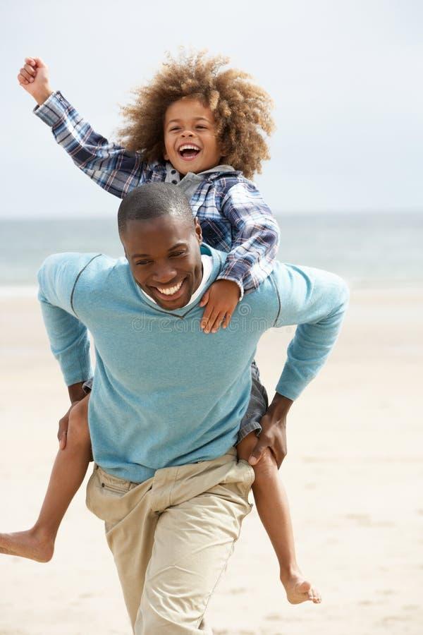 Παιχνίδι πατέρων και γιων piggyback στην παραλία στοκ φωτογραφία