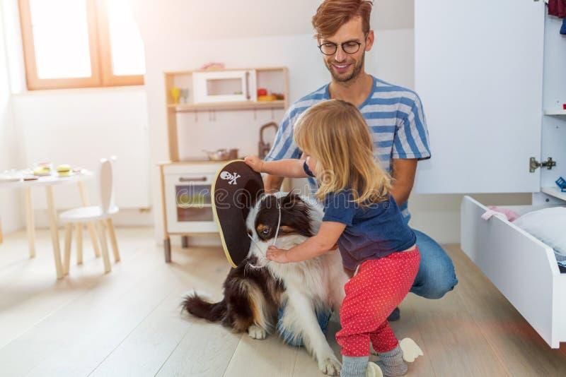 Παιχνίδι πατέρων και κορών φόρεμα-επάνω με το σκυλί στοκ εικόνες