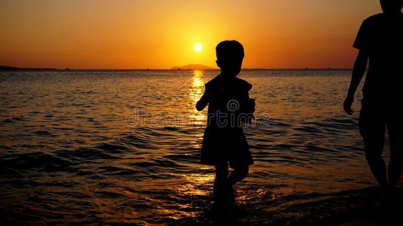 Παιχνίδι πατέρων και παιδιών στην παραλία στο χρόνο ηλιοβασιλέματος Έννοια της οικογένειας στοκ φωτογραφίες