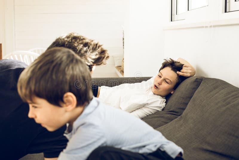 Παιχνίδι πατέρων με τα παιδιά του στον καναπέ στο σπίτι στοκ φωτογραφίες