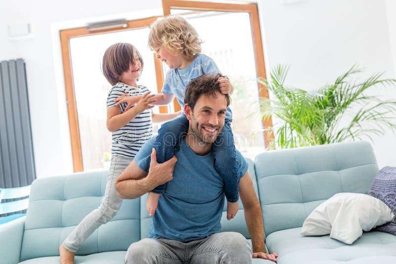 Παιχνίδι πατέρων με τα παιδιά του στο σπίτι στοκ φωτογραφίες